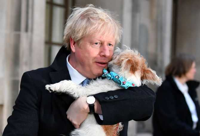 Britain's Prime Minister Boris Johnson holds his dog Dilyn as he leaves a polling station